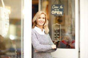 A business owner stands in front of her store.